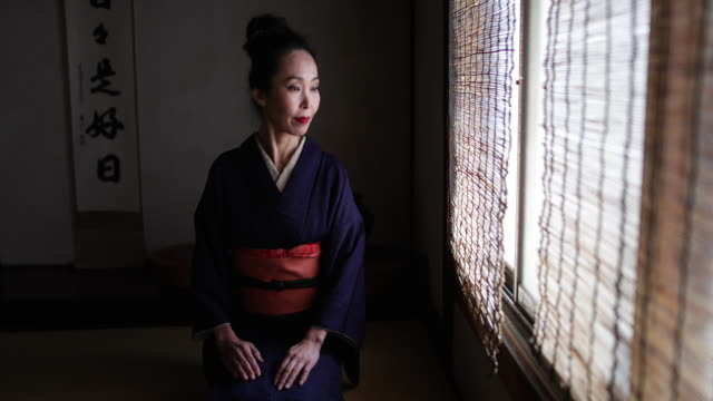 portrait of japanese woman wearing kimono by traditional window looking to camera, kyoto japan - mystery stock videos & royalty-free footage