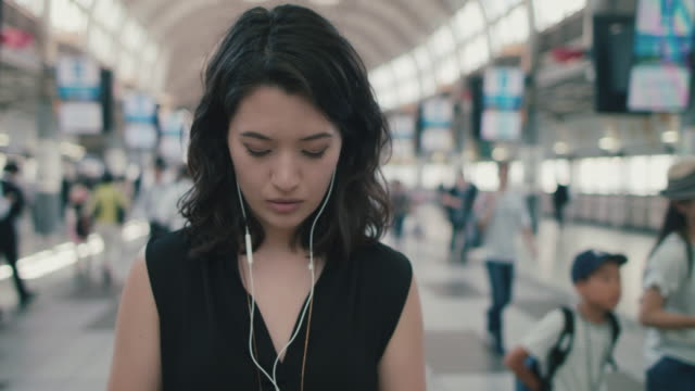 portrait of japanese woman with headphones standing in busy train station in tokyo, japan - headphones stock videos & royalty-free footage