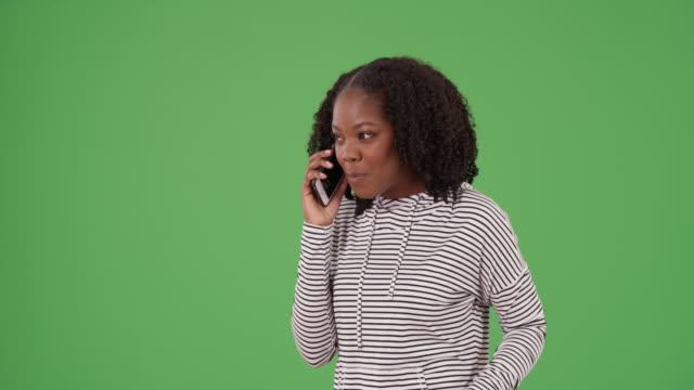 portrait of joyful black female talking to boyfriend on phone on green screen - {{asset.href}} stock videos & royalty-free footage