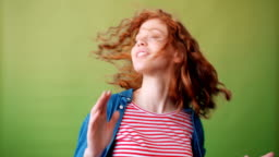 Portrait of joyful red-haired girl dancing and smiling on green background