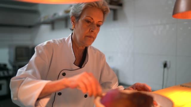 vidéos et rushes de verticale de chef de cuisine utilisant des pincettes pour finaliser un plat - cuisinière