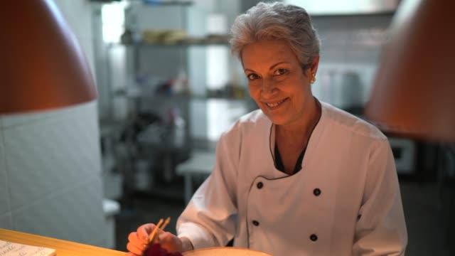 porträt des küchenchefs mit einer pinzette, um ein gericht fertigzustellen - fachberuf stock-videos und b-roll-filmmaterial