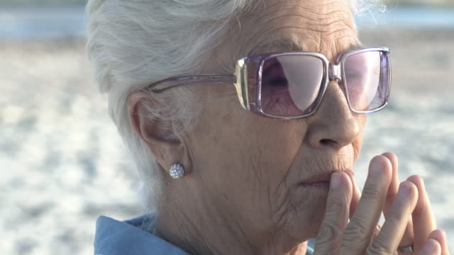 Portrait of lady with stylish glasses on the beach with hands in mouth and white hair, natural light