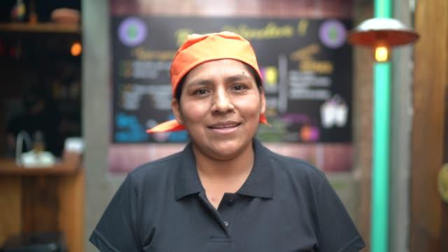 vídeos de stock e filmes b-roll de portrait of latin waitress looking at camera - empregada de mesa