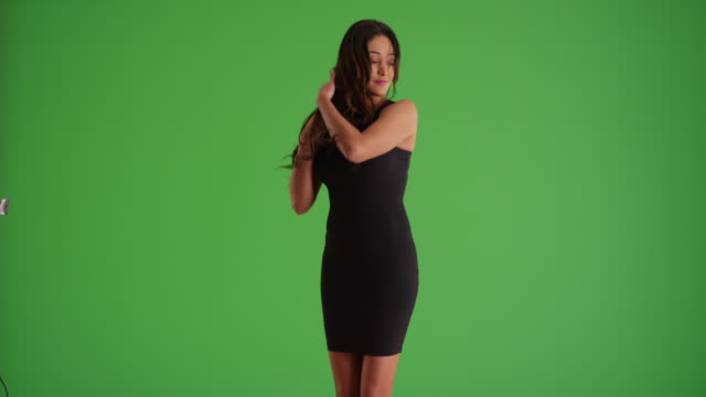 portrait of latina female in tight black dress dancing sensually on green screen - black dress stock videos & royalty-free footage