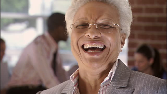 cu, r/f, portrait of laughing senior businesswoman holding fan of money, colleagues in background, los angeles, california, usa - exhilaration stock videos & royalty-free footage