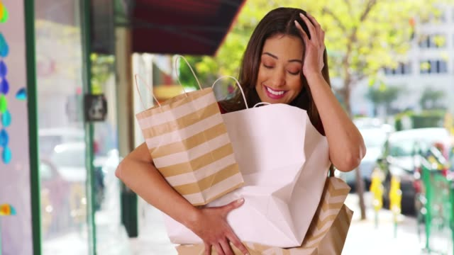 stockvideo's en b-roll-footage met portrait of laughing shopaholic struggling to carry her purchases outside store - shopaholic