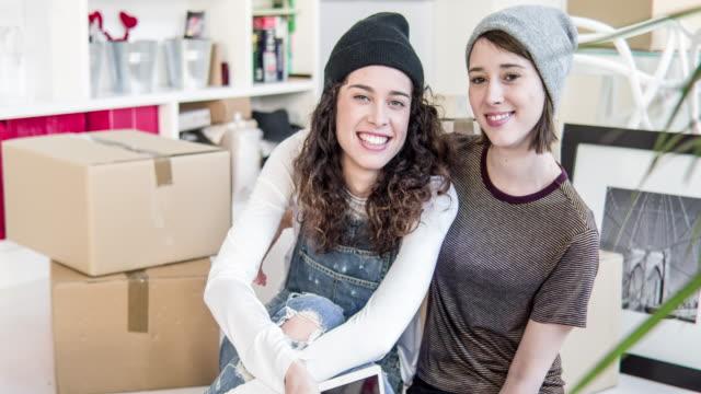 vídeos de stock, filmes e b-roll de retrato de casal de lésbicas carinhos enquanto descompactar para a nova casa - homossexualidade