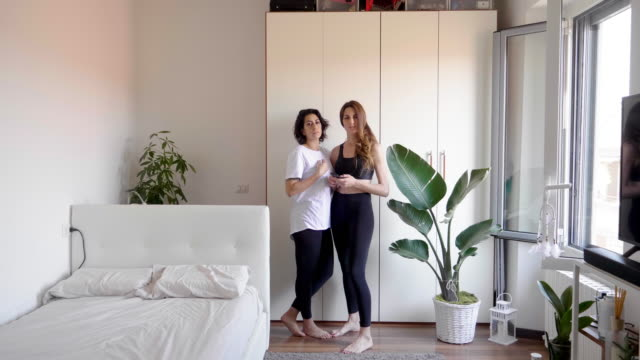 portrait of lesbian couple standing in bedroom - mid length hair stock videos & royalty-free footage