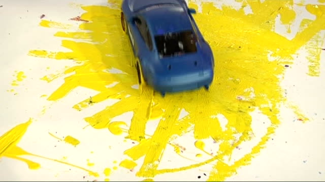 portrait of lewis hamilton painted using remote controlled cars reporter to camera cutaway remotecontrolled car moving on yellow paint close up eyes... - remote controlled stock videos and b-roll footage