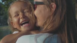 Portrait of little laughing child girl in her mother's hugs outdoor