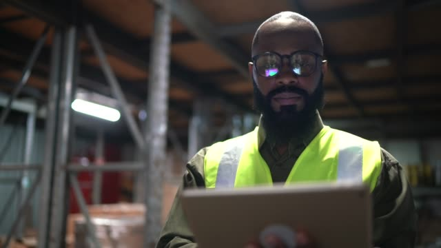 portrait of logistics employee using digital tablet at warehouse - warehouse stock videos & royalty-free footage