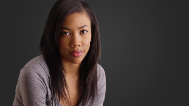portrait of lovely black female with gentle smile on gray background - körperpflege stock-videos und b-roll-filmmaterial