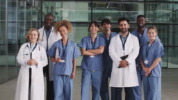 Portrait of male and female medical team standing in modern hospital building - shot in slow motion