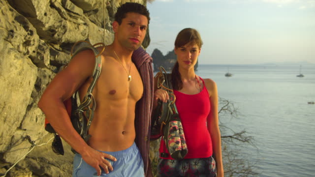 ms portrait of male and female rockclimbers with climbing equipments standing by rock facerock face, ocean and pinnacles in background / krabi, thailand - rock face stock videos & royalty-free footage