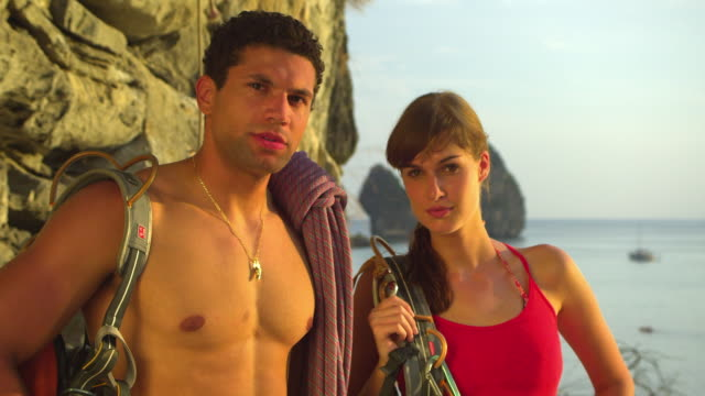 cu portrait of male and female rockclimbers with climbing equipments standing by rock facerock face, ocean and pinnacles in background / krabi, thailand - rock face stock videos & royalty-free footage
