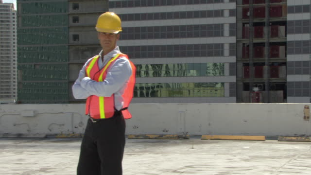 ms ds portrait of male architect wearing reflecting vest and hardhat at construction site / miami, florida, usa - helm stock-videos und b-roll-filmmaterial