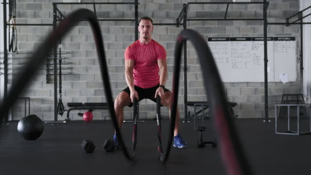 portrait of male athlete doing biceps wave with battle ropes - rope stock videos & royalty-free footage