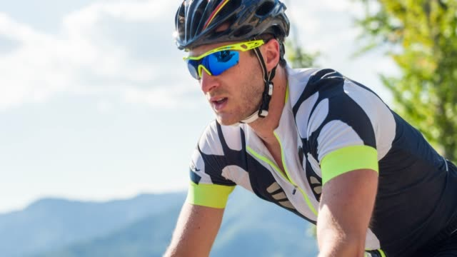 portrait of male athlete road cycling on a hot sunny day - cycling helmet stock videos & royalty-free footage