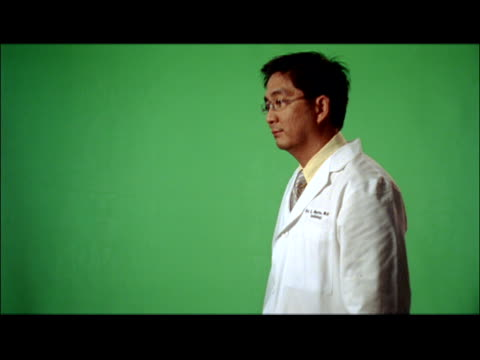 ms, portrait of male doctor against green background - överkroppsbild bildbanksvideor och videomaterial från bakom kulisserna