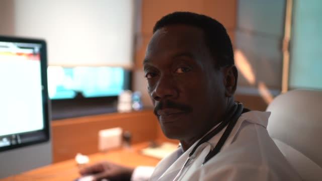 医師室でデスクトップコンピュータを使用した男性医師の肖像画 - 努力点の映像素材/bロール