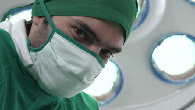 portrait of male doctor wears a surgical gown in the operating room (face close-up) - operating gown stock videos & royalty-free footage