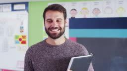 Portrait Of Male Elementary School Teacher Standing In Classroom