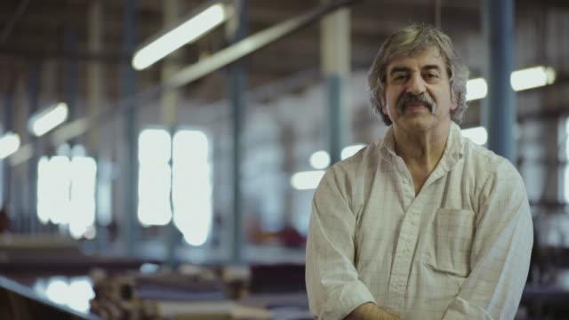 vídeos de stock e filmes b-roll de portrait of male factory worker leaning on large desk - textile factory
