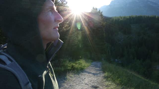 stockvideo's en b-roll-footage met portret van mannelijke wandelaar dragen hoody in bergen, zonsopgang - zichtbare adem