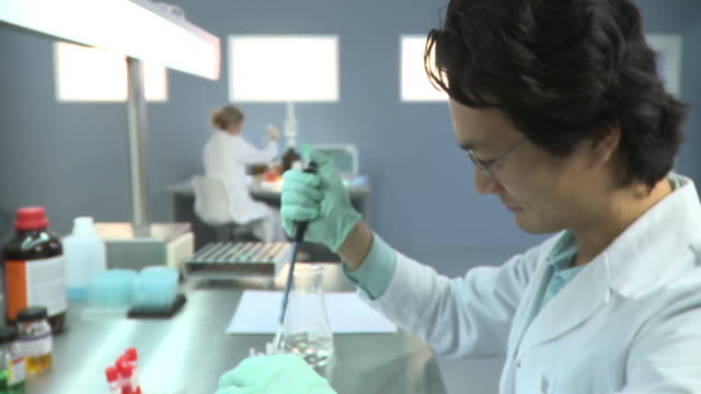 cu portrait of male lab technician using dropper to put samples into vials in lab, woman in background / berlin, germany - lab coat stock videos & royalty-free footage