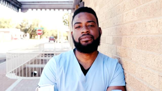 portrait of male nurse outside hospital building - male nurse stock videos & royalty-free footage