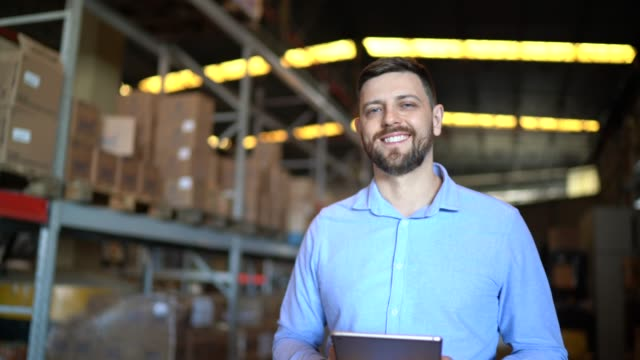 portrait of male warehouse worker using digital tablet - warehouse stock videos & royalty-free footage