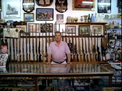 WS, Portrait of man behind glass case at gun shop, Tonopah, Nevada, USA