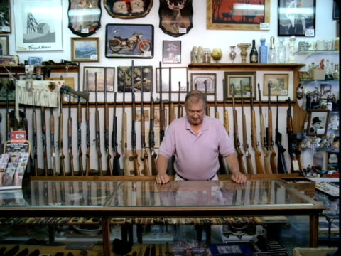 ws, portrait of man behind glass case at gun shop, tonopah, nevada, usa - gun shop点の映像素材/bロール