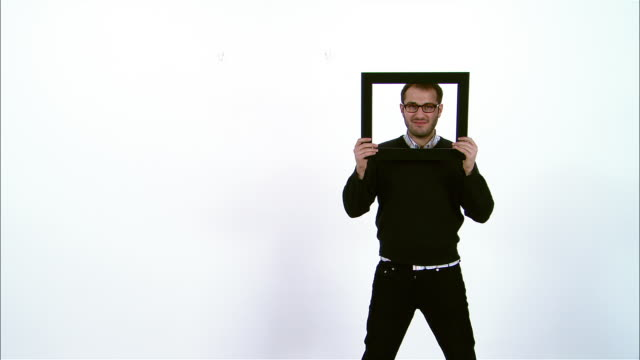 portrait of man holding and looking through picture frame - hair stubble stock videos & royalty-free footage