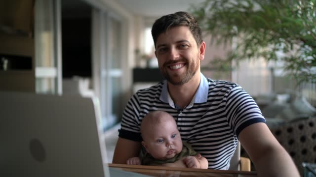 vídeos de stock, filmes e b-roll de retrato de homem segurando seu filho e trabalhando com laptop em casa - assistência