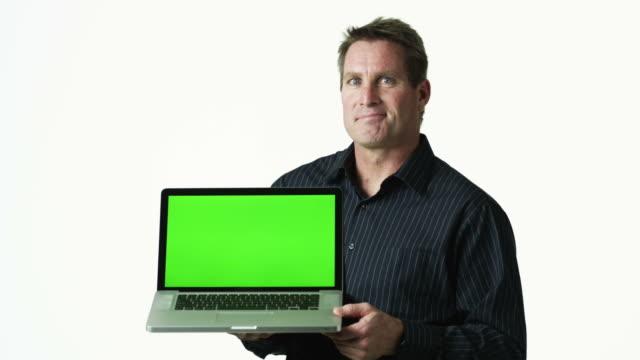 ms portrait of man holding laptop against white background / orem, utah, usa - orem utah stock videos & royalty-free footage
