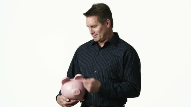 ms portrait of man holding piggy bank against white background / orem, utah, usa - orem bildbanksvideor och videomaterial från bakom kulisserna