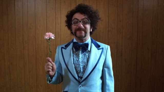 MS Portrait of man in blue suit holding pink carnation and waving, Atlanta, Georgia, USA