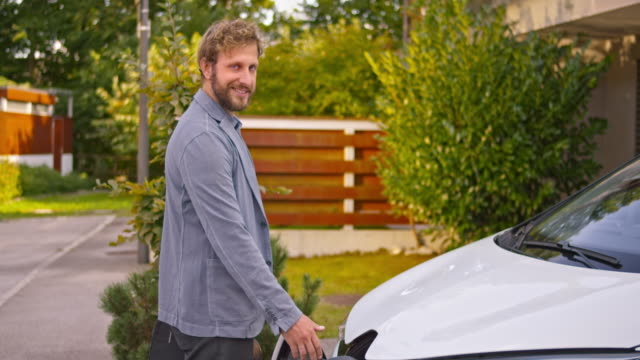 slo mo portrait of man inserting plug into electric car - sustainable tourism stock videos & royalty-free footage