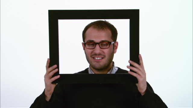 Portrait of man looking through picture frame