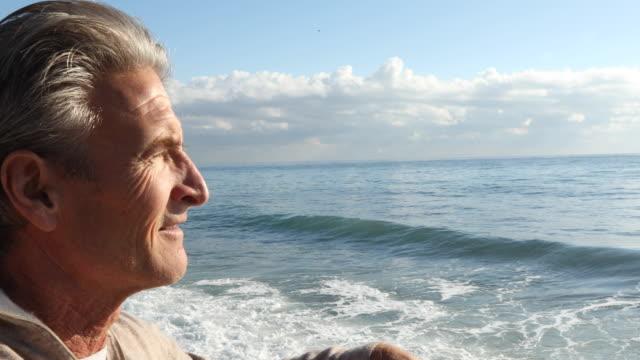 portrait of man relaxing near surf's edge - uomo maturo video stock e b–roll