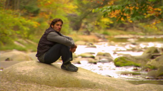 ws, portrait of man sitting by forest river, autumn, phoenicia, new york, usa - アルスター郡点の映像素材/bロール
