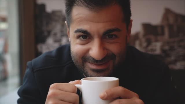 vidéos et rushes de verticale d'homme s'asseyant près de la fenêtre et buvant le thé au café - café boisson