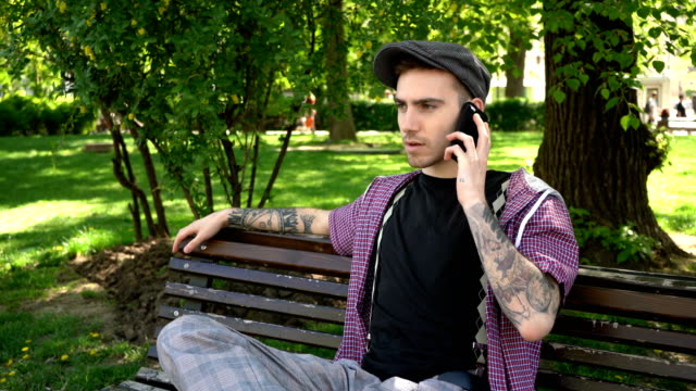 portrait of man sitting on a park bench, talking on the phone - anxiety stock videos & royalty-free footage