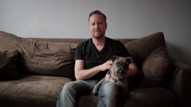 Portrait of man sitting on couch with dog looking at camera