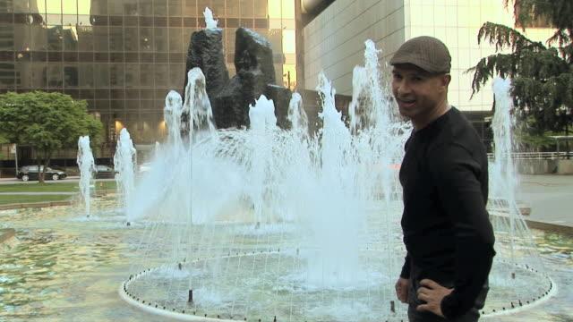 vidéos et rushes de ms portrait of man standing in front of fountain, vancouver, british columbia, canada - cadrage aux genoux