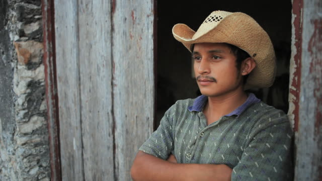 stockvideo's en b-roll-footage met ms portrait of man standing in open doorway with arms crossed, izamal, yucatan, mexico - cowboyhoed