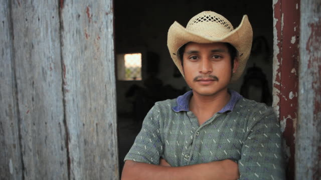 stockvideo's en b-roll-footage met ms portrait of man standing in open doorway with arms crossed, walks into stable, izamal, yucatan, mexico - cowboyhoed