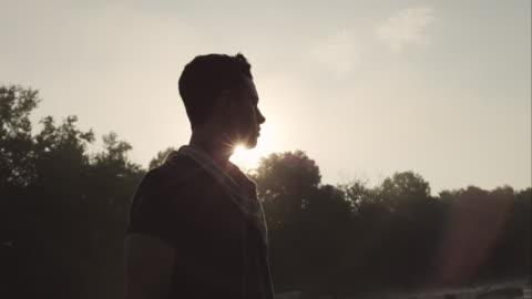 portrait of man standing on large rock in river at sunrise - motljus bildbanksvideor och videomaterial från bakom kulisserna